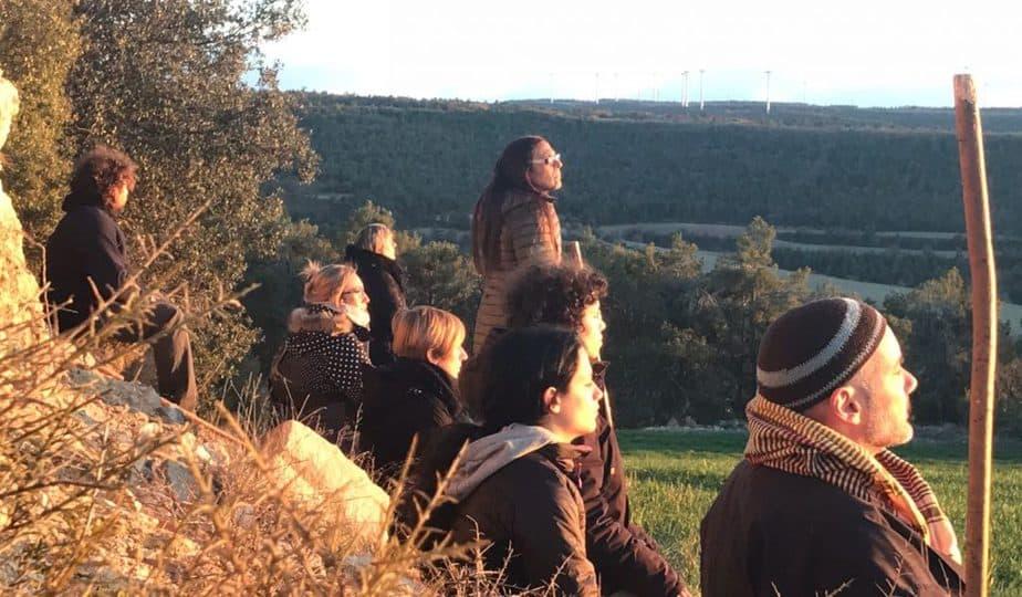 Participantes sentados frente a una puesta de sol en nuestro retiro de meditación y creatividad, en el Ashram de la Creativitat, Segura, Tarragona
